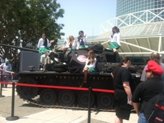 Cosplayers climb on a replica tank outside the convention center.