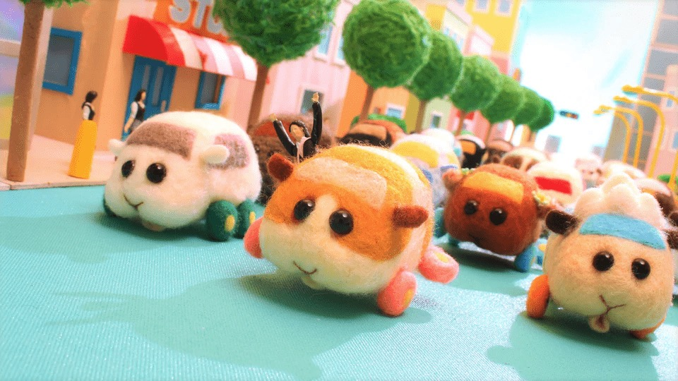 A stampede of felt guinea pig car plushies driving down the street.
