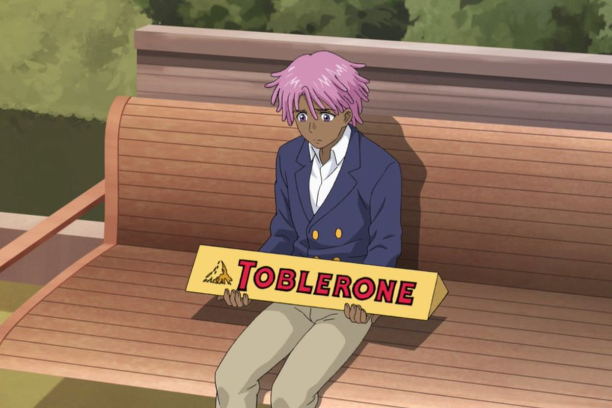 Kaz Kaan sitting on a park bench, holding a big Toblerone
