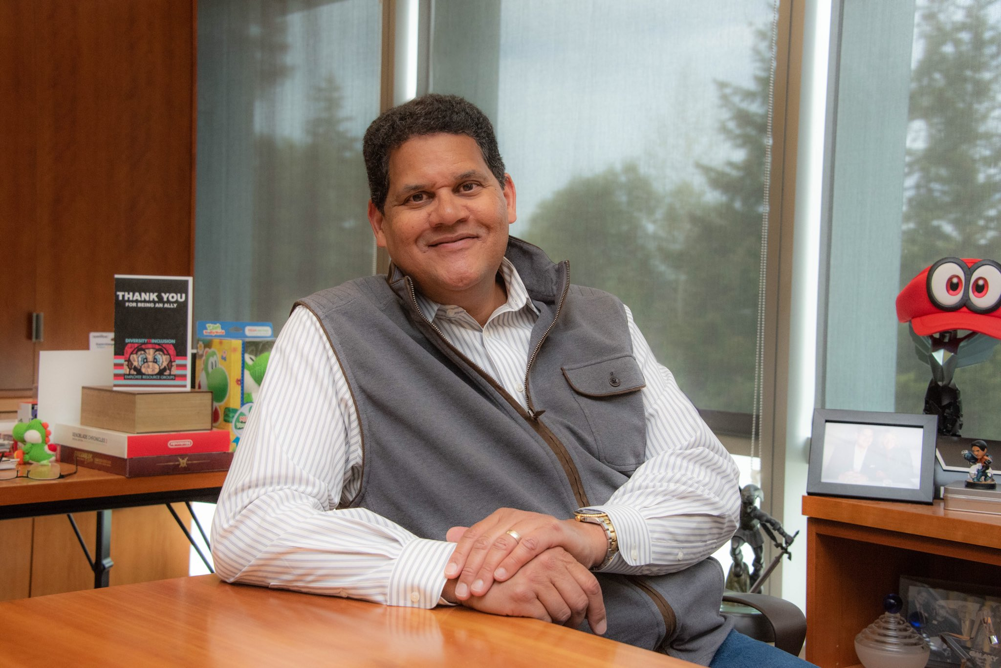 Reggie Fils-Aime sitting at his desk, smiling. There is Nintendo paraphernalia on the shelves behind him.