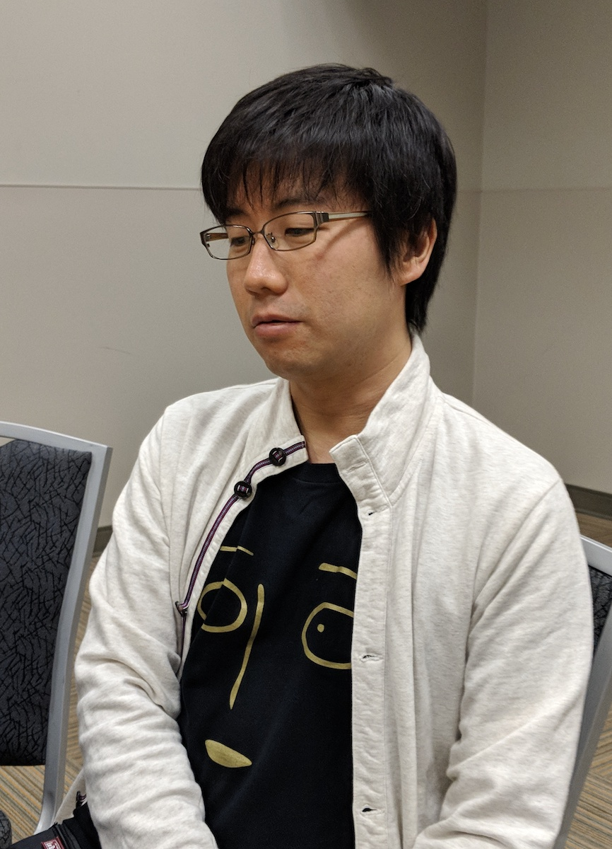 Chikashi Kubota sitting in a chair, wearing a t-shirt with the face of Saitama from One-Punch Man
