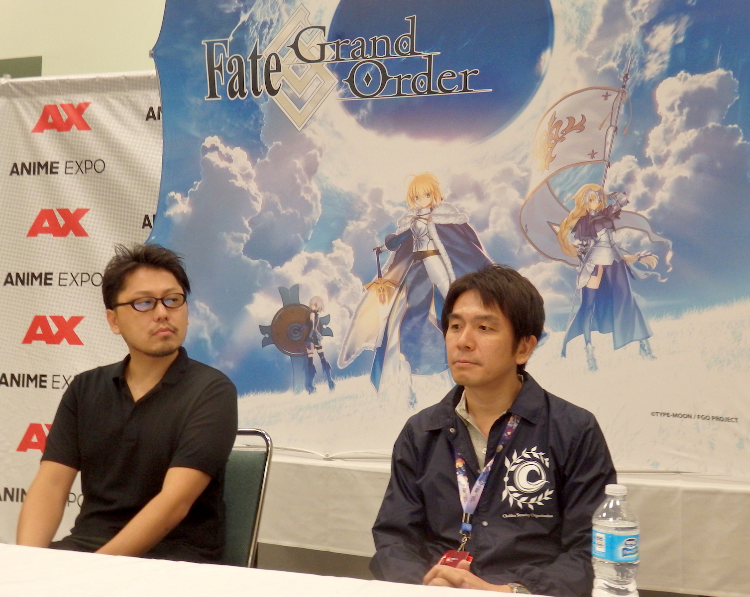 Two Japanese men sitting at a table in front of a banner for Fate: Grand Order.