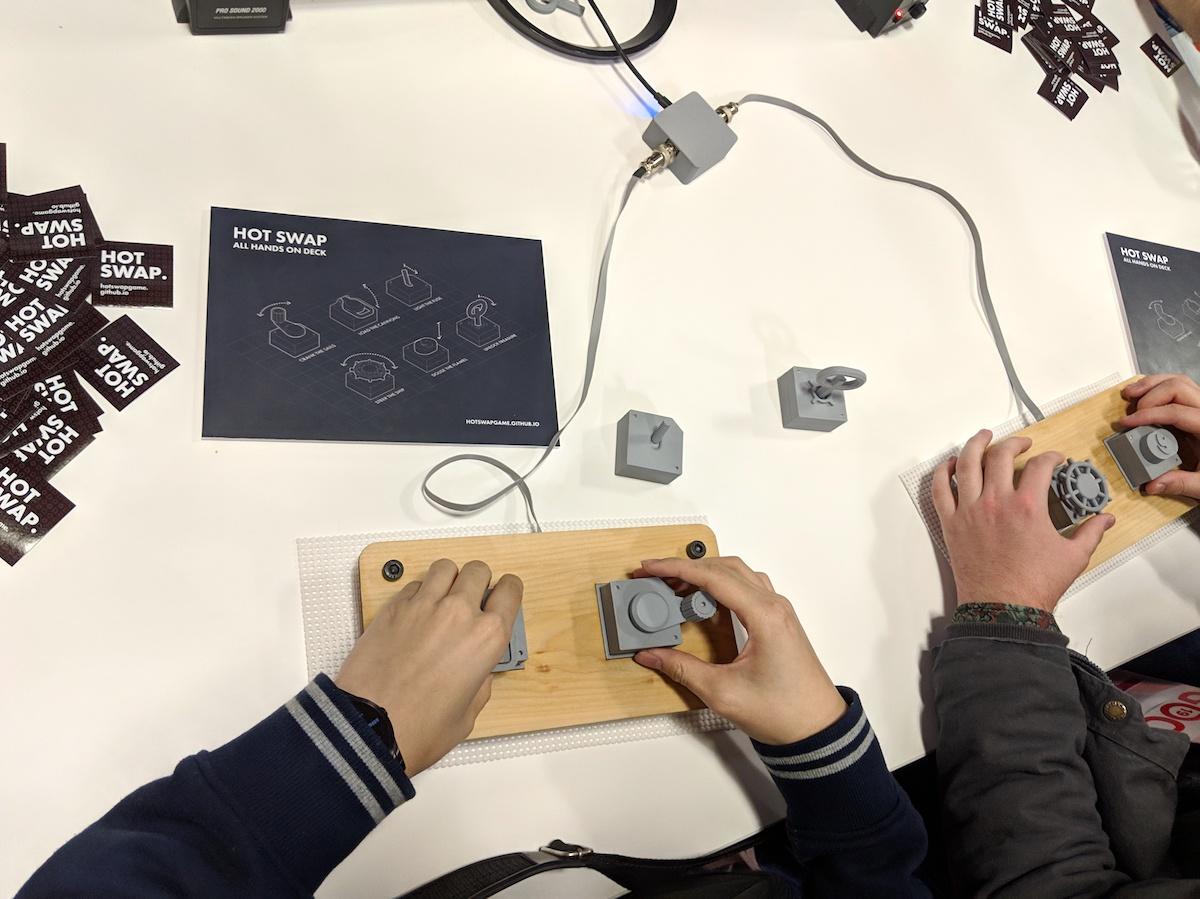 Two people playing Hot Swap, moving around gray button pieces in front