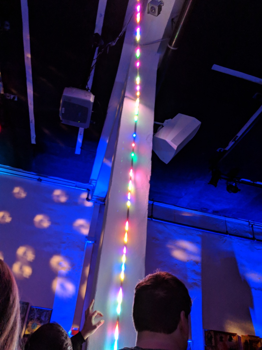 A multicolored LED strip running up the wall in a bar.