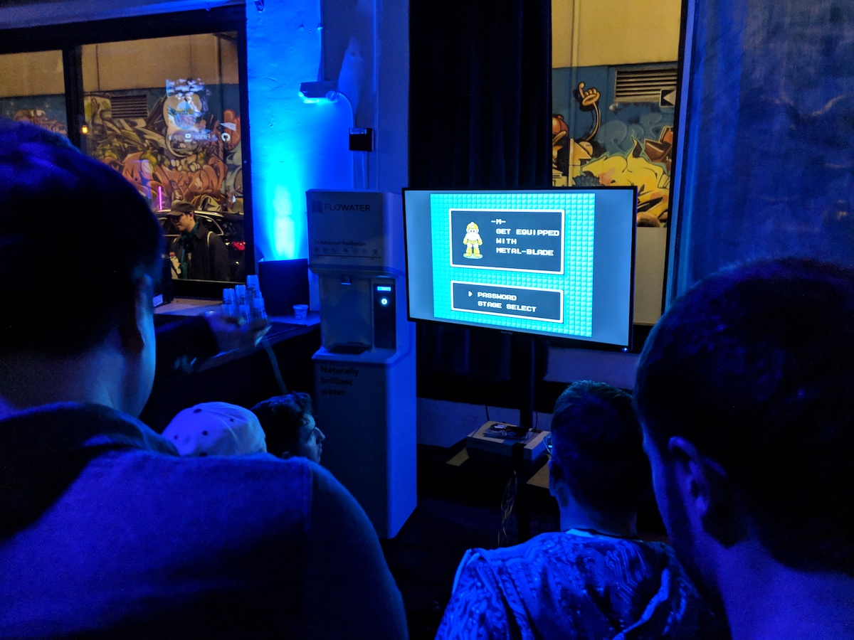 A group of people sitting around a TV with Megaman on it.