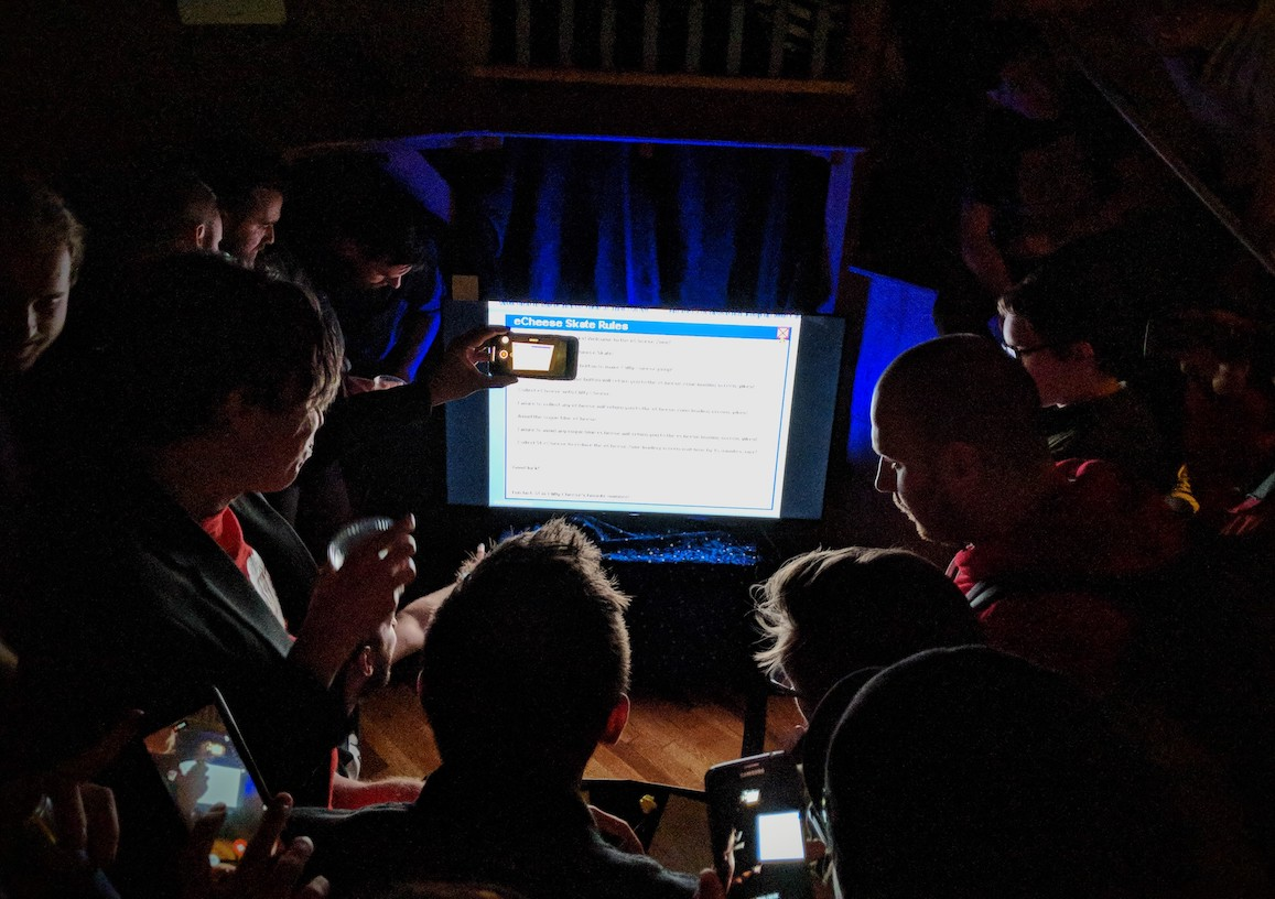 Game developers crowding around a screen playing E-Cheese Zone in a dark room at a party