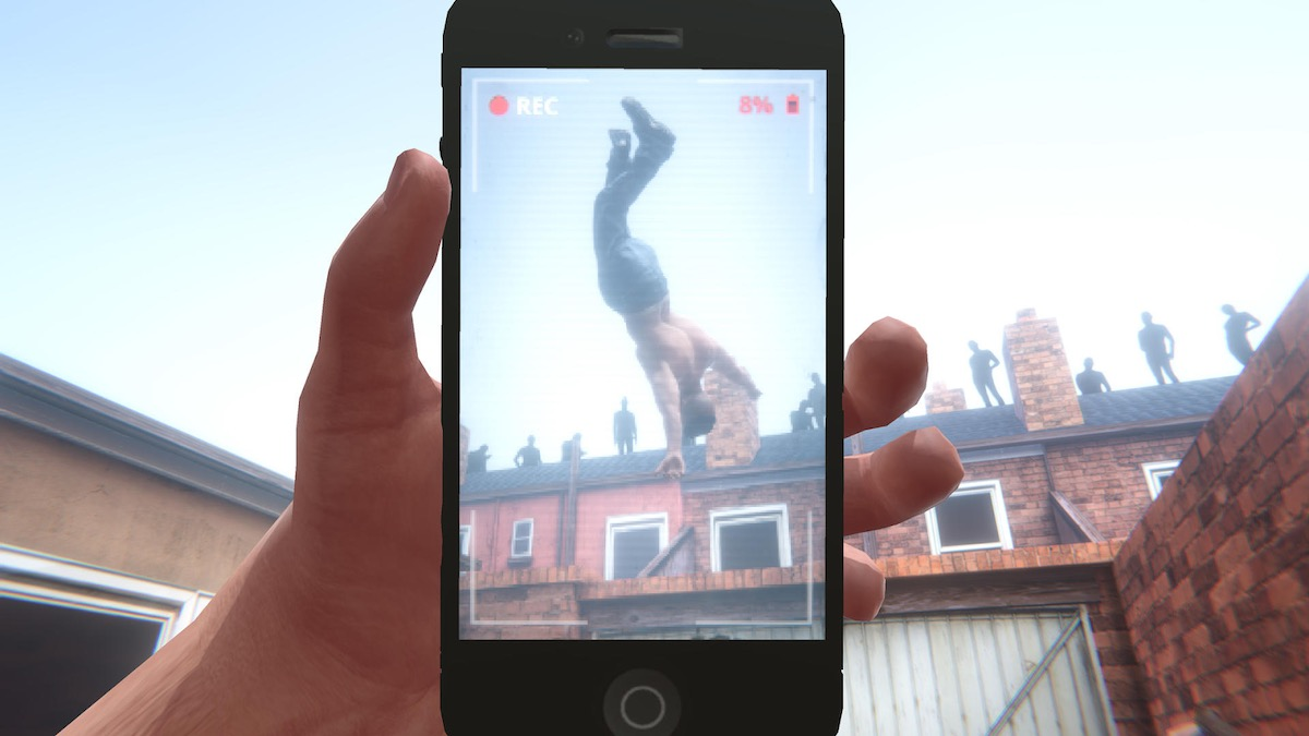 A shirtless young man flipping in the air while being recorded by a cell phone.