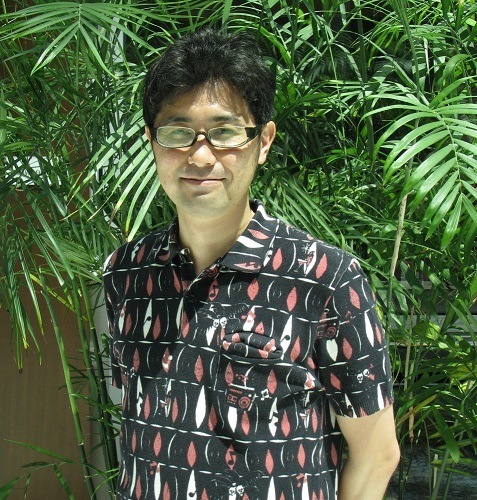 Yoshiaki Kyougoku, a thin middle-aged Japanese man in a button-down shirt, smiling.