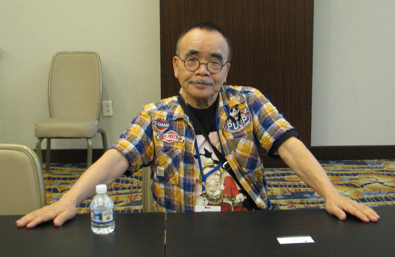Masao Maruyama, a short, elderly Japanese man, sitting at a table with his arms spread out.