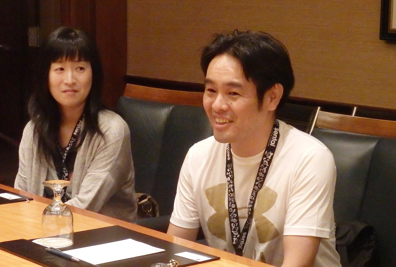 A Japanese woman and man sitting at a table. The main is smiling and talking.