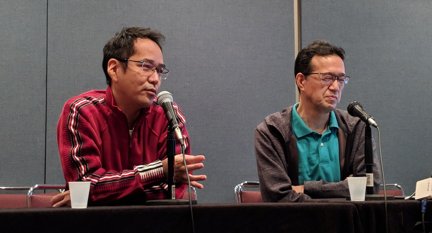 Kenji Kamiyama speaking on a panel with Shinji Aramaki sitting to his left