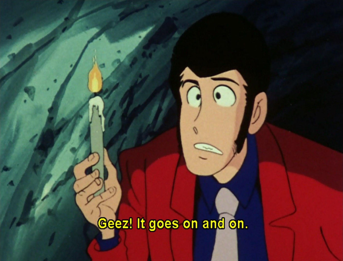 "Red Jacket Lupin holding a candle in a cave. He says ""Geez! It goes on and on."""