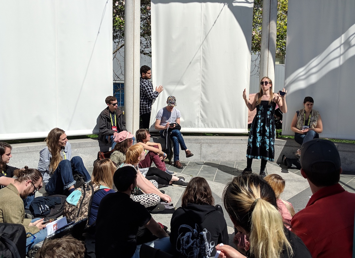 Young woman standing in a plaza outside, speaking and holding her hands up while a crowd of young people sits in a circle watching her.