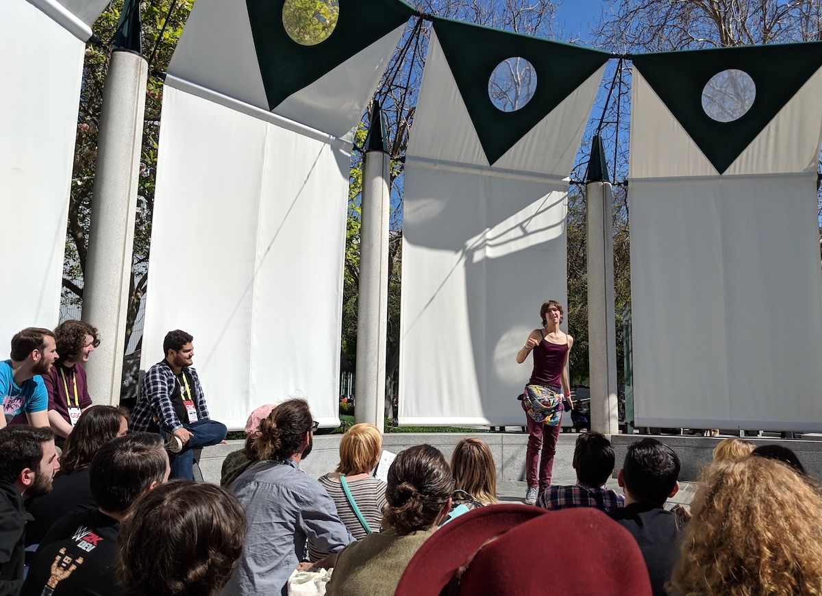 Young person standing in a plaza outside, speaking and holding their hand up while a crowd of young people sits in a circle watching them.