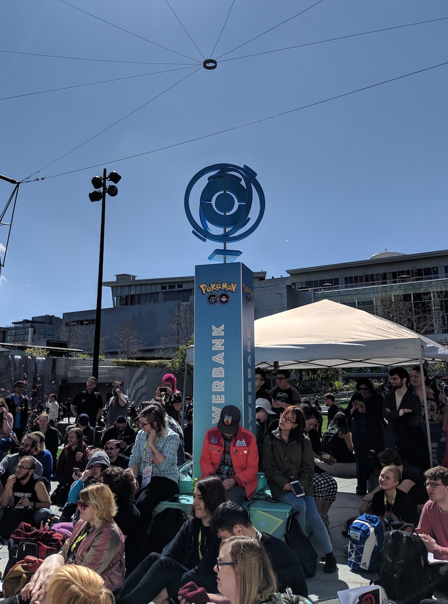 Crowd of young people sitting on the ground outside. In the center is a Pokémon Go-branded tower labeled