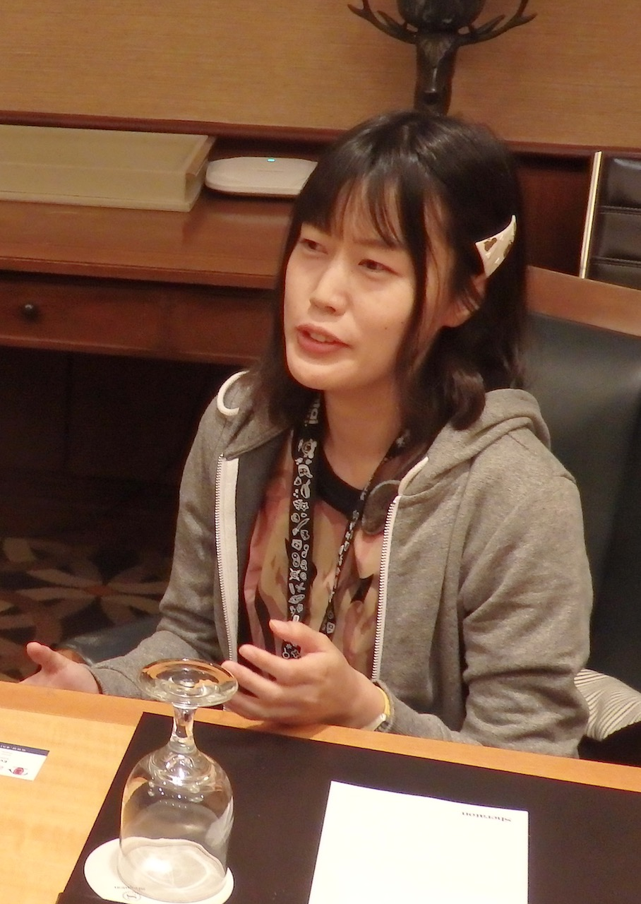 A young Japanese woman sitting at a table talking