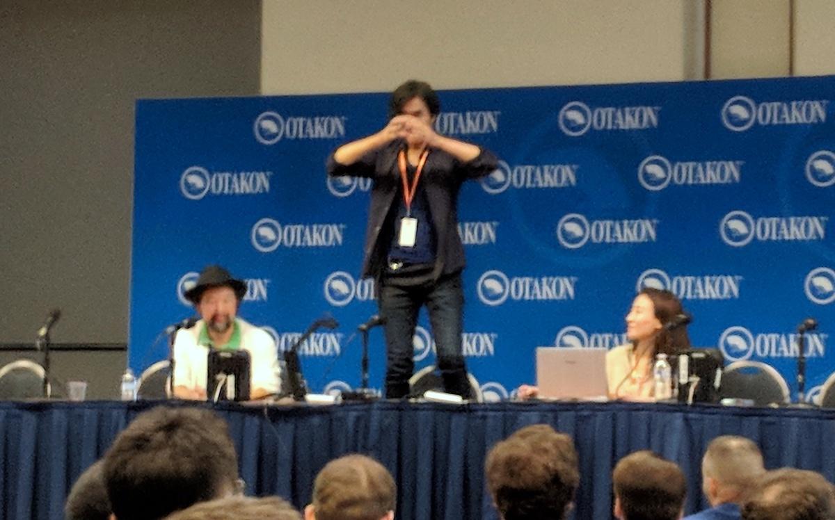Shoji Kawamori standing up on the table at his panel
