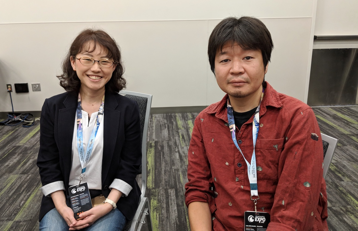 Rie Ogura, wearing a blazer and glasses, and Yoshitoshi ABe, wearing a red button-down shirt