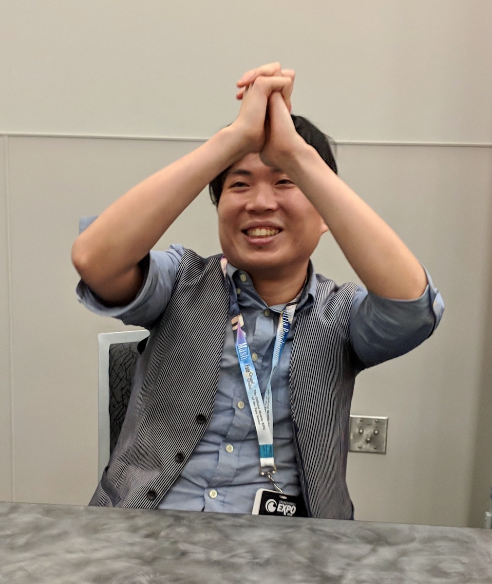 Shingo Yamashita miming a dance with his hands clasped and held over his head