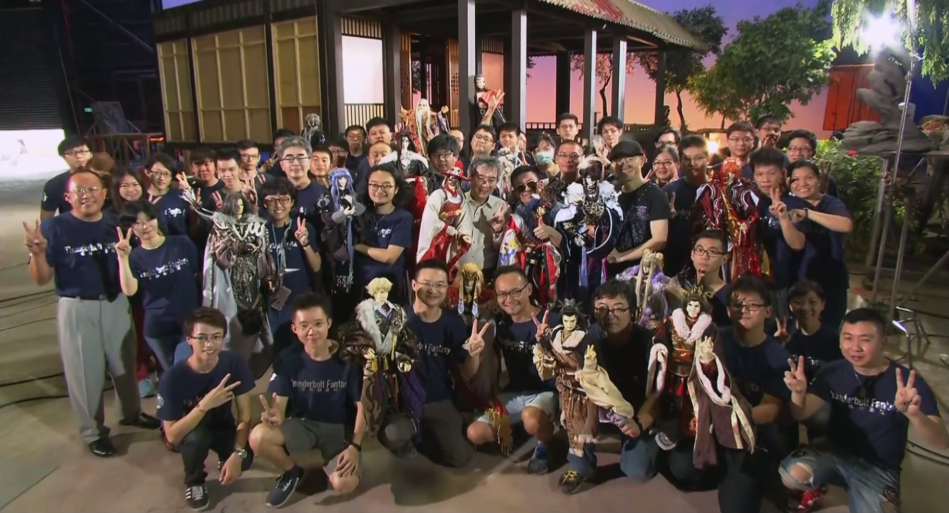 The cast and puppets of Thunderbolt Fantasy arranged bleacher style in a group photo at the wrap of show.