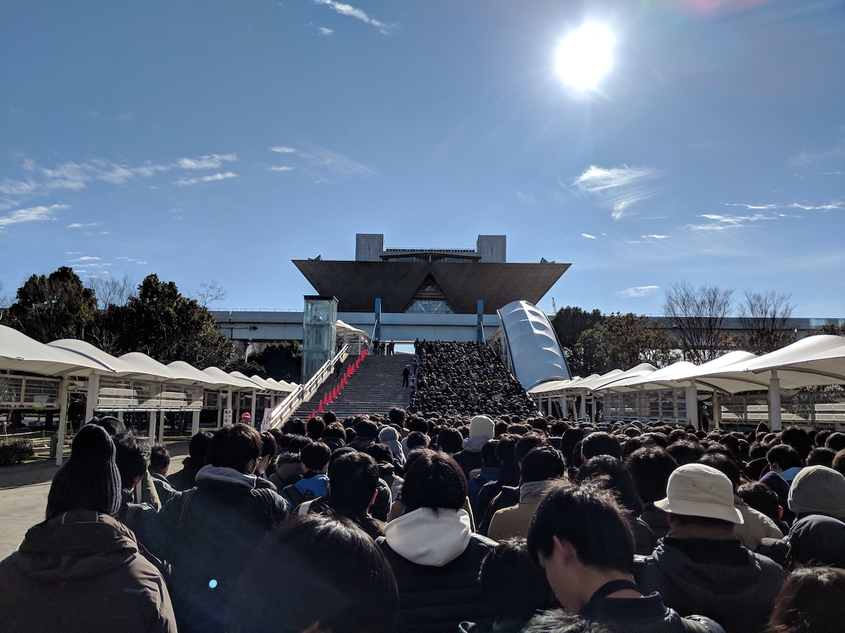 Massive crowd of hundreds of people walking down a pathway and up a stairwell toward the Tokyo Big Sight. There are blue skies overhead with a few wispy clouds.