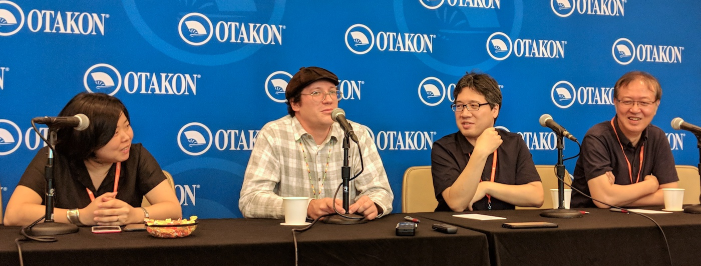Tsutsumi, Yoshinari, and Otsuka laugh while on stage in front of an Otakon banner