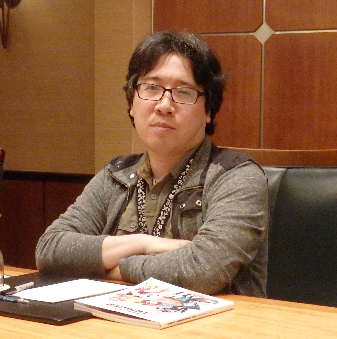 Yoshinari sitting at a table with his arms crossed.