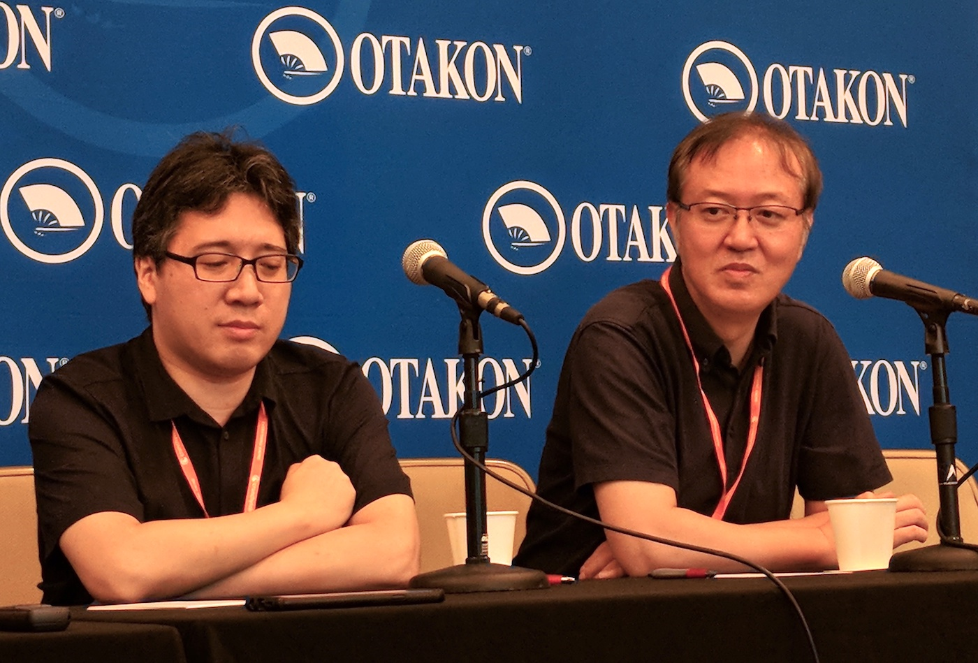 Yoshinari and Otsuka sitting in front of an Otakon banner, thinking